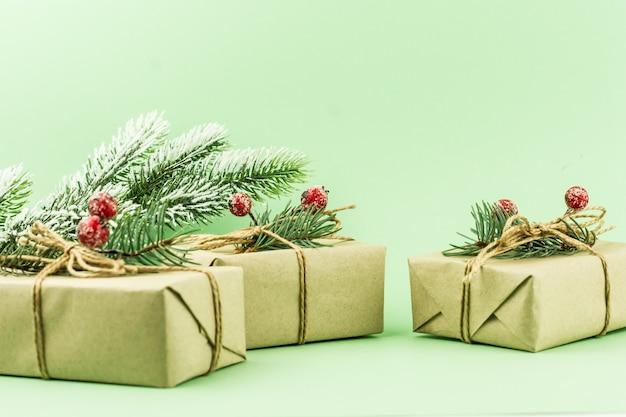 Tre regali di capodanno festosi confezionati in carta artigianale con decorazioni di rami di abete rosso e bacche. angolo ravvicinato.
