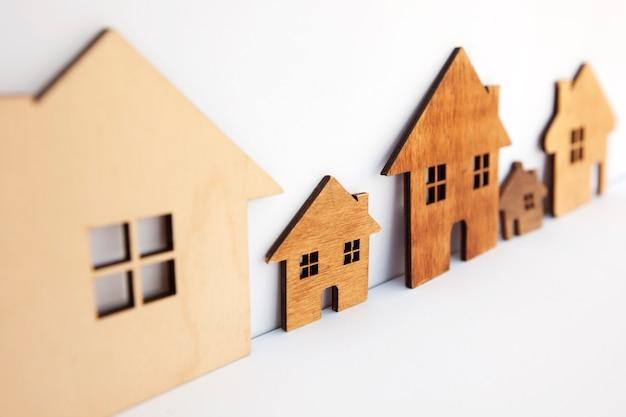 Tre case in legno piatte isolate sul tavolo bianco