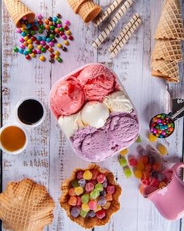Tre gusti di gelato in un contenitore di consegna, realizzando una composizione con diversi coni e gomme colorate. vista dall'alto