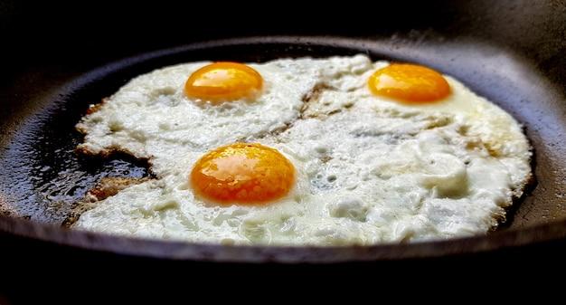 Tre uova fritte ruspanti in una padella antiaderente calda.