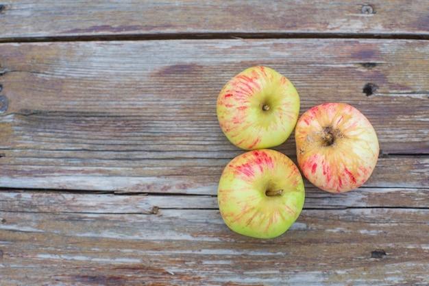 Tre mele fresche giacciono su una superficie di legno. concetto di cibo sano.