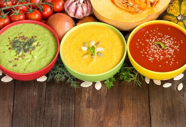 Tre zuppe di verdure colorate fresche - pomodoro, zucca e piselli su un tavolo di legno