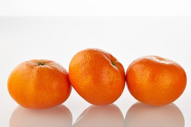 Tre frutti di mandarini succosi freschi isolati su sfondo bianco.