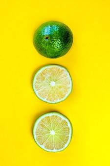 Tre spicchi di lime affettati freschi si trovano verticalmente in una riga