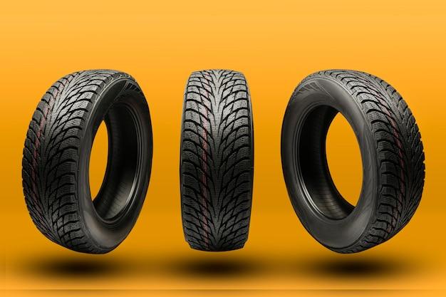 Tre pneumatici a frizione, riavvio stagione invernale, su sfondo arancione brillante.