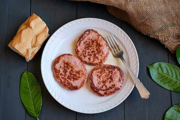 Tre hamburger di carne di pollo fritto, su piatto bianco visto dall'alto