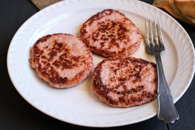 Tre hamburger di carne di pollo fritto, su piatto bianco