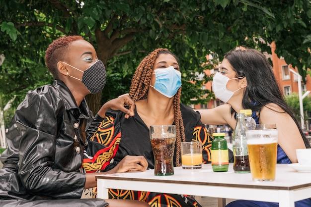 Tre amici sulla terrazza di un bar bevono un drink divertendosi con le maschere per il viso a causa della pandemia di coronavirus covid 19
