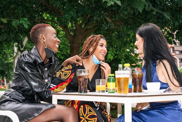 Tre amici sulla terrazza di un bar bevono un drink divertendosi con le maschere per il viso a causa della pandemia di coronavirus