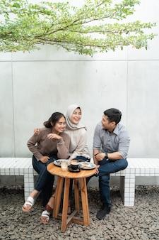 Tre amici si godono il caffè insieme nella caffetteria