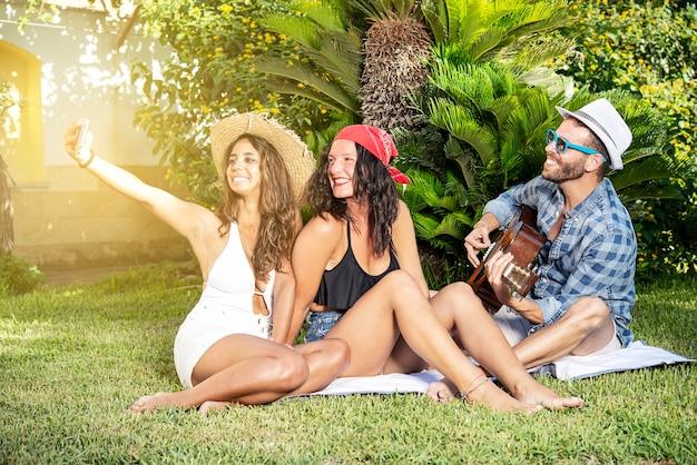 Tre amici sull'erba che suonano la chitarra e si fanno un selfie. concetto di amicizia