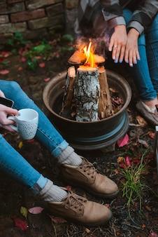 Tre amici si rilassano comodamente e bevono vino in una serata autunnale all'aria aperta accanto al fuoco nel cortile di casa.