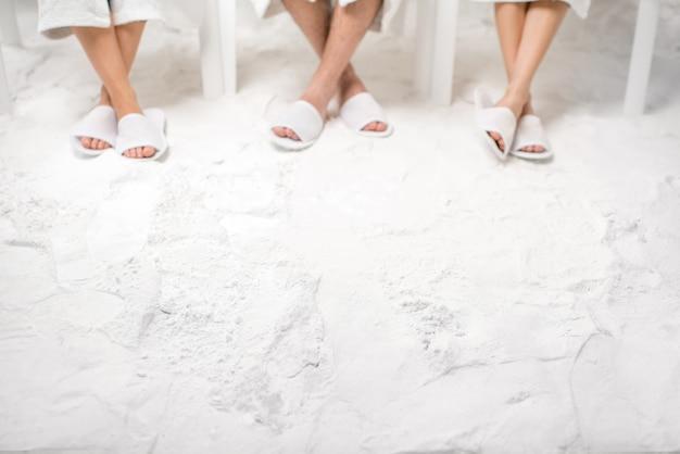 Tre amici che si rilassano nella stanza del sale. vista ravvicinata sulle gambe con copia spazio