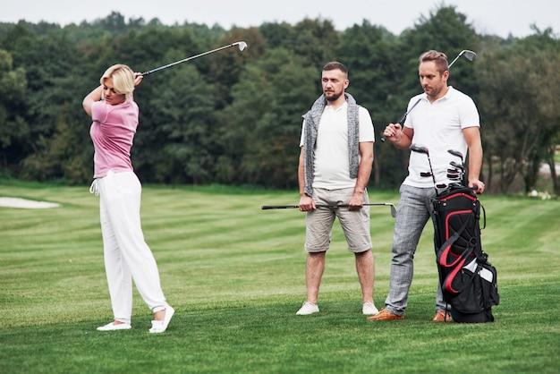 Tre amici che trascorrono del buon tempo sul campo giocando a golf e guardando lo scatto.
