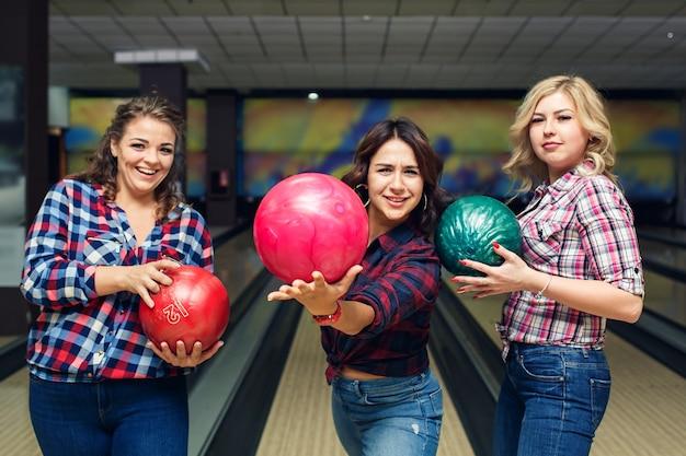 Tre amiche attraenti divertenti tengono le palle da bowling
