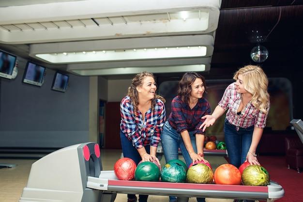 Tre amiche attraenti divertenti prendono le palle da bowling.