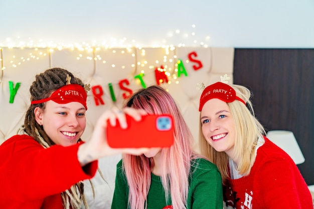 Tre ragazze divertenti in maglioni natalizi si fanno dei selfie. foto di alta qualità