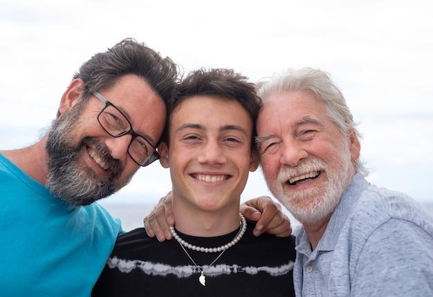 Tre generazioni di famiglia, abbraccio sorridente felice, padre, figlio adolescente e nonno. belle persone che si divertono insieme