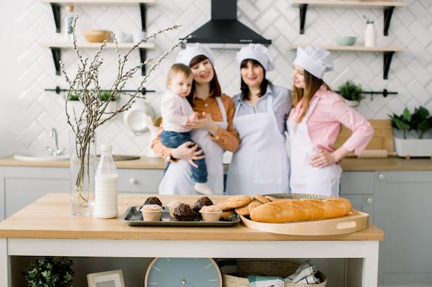 Tre generazioni di donne cucinano in cucina, si concentrano sul tavolo con maffine e biscotti. cibo fatto in casa e piccolo aiuto. famiglia felice. cottura in cucina. vacanze di pasqua o festa della mamma