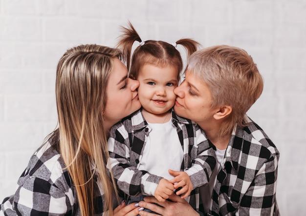 Tre generazioni di donne si abbracciano contro una superficie bianca. immagine di famiglia