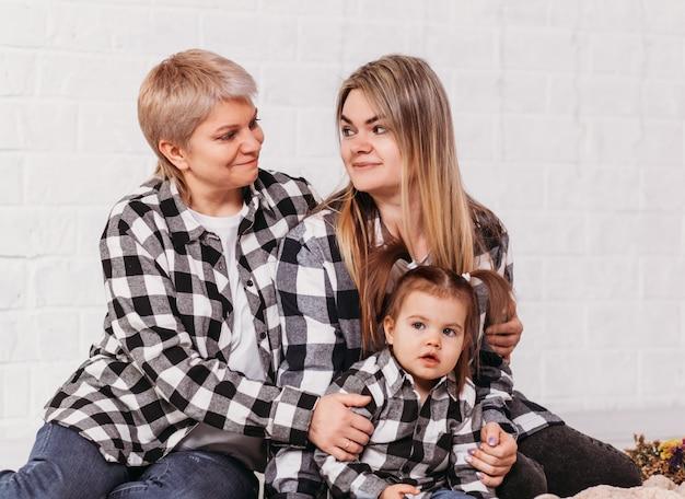 Tre generazioni di donne si abbracciano e si guardano su una superficie bianca