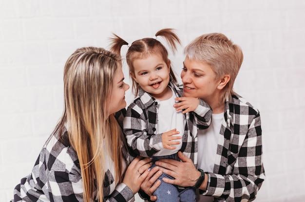 Tre generazioni di donne, madre, nonna e nipote in famiglia guardano su una superficie bianca