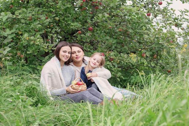 Tre generazioni di donne della stessa famiglia nel frutteto di mele al picnic