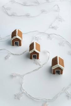 Tre case di marzapane per tazza su sfondo bianco con ghirlande. prodotti da forno di natale.