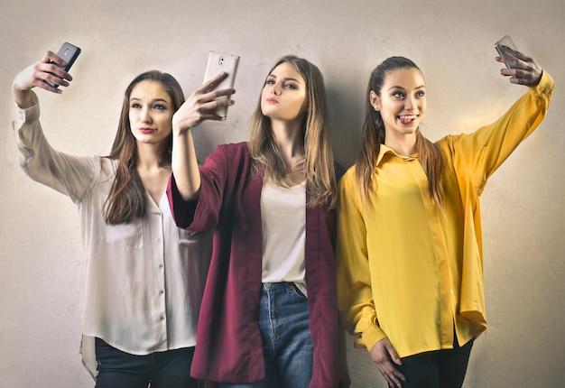 Tre ragazza prende un selfie