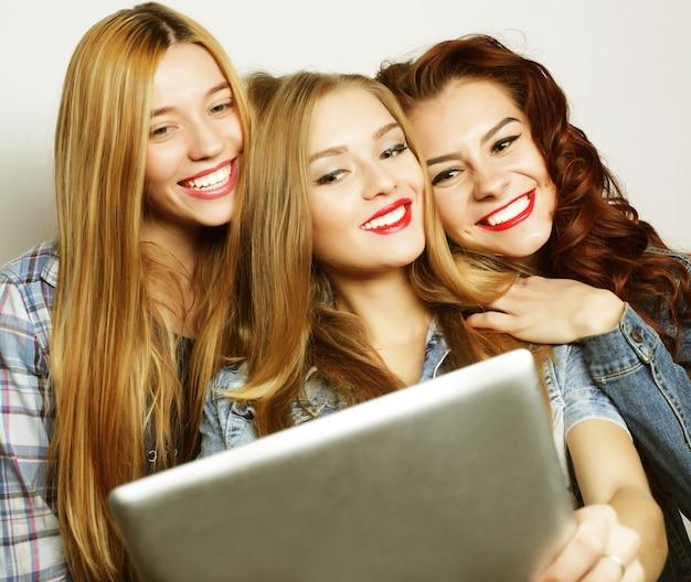 Tre amiche che prendono selfie con la tavoletta digitale