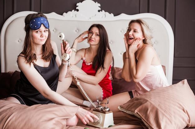 Tre ragazze di un amico hanno organizzato un pigiama party su un letto di peluche. le ragazze scherzano e fingono di parlare su un telefono retrò.