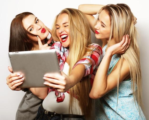 Tre amiche che si fanno selfie con tavoletta digitale, su grigio