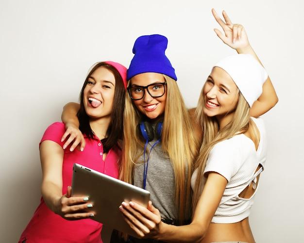 Tre amiche che prendono selfie con tavoletta digitale, studio girato su sfondo grigio