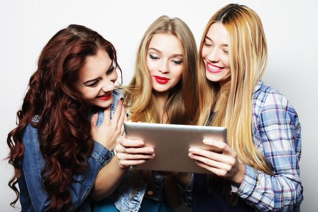 Tre amiche che si fanno selfie con tavoletta digitale, foto in studio su sfondo grigio Foto Premium