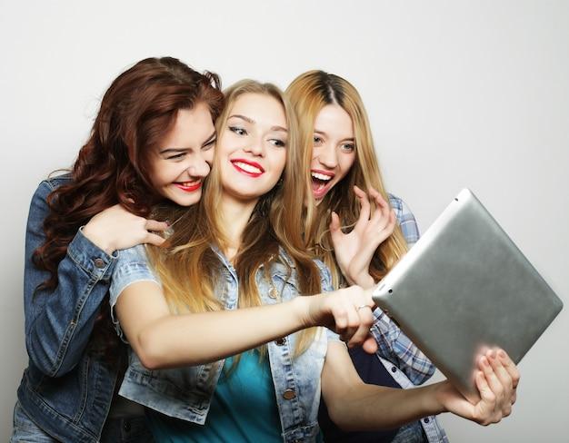 Tre amiche che si fanno selfie con tavoletta digitale, foto in studio su sfondo grigio