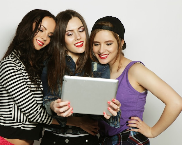 Tre amiche che prendono selfie con tablet digitale, studio girato su vackground grigio