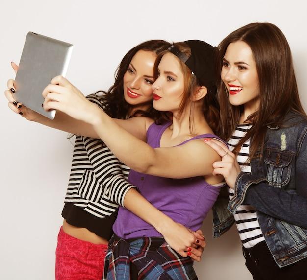 Tre amiche che si fanno selfie con una tavoletta digitale