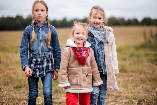 Tre ragazze sorelle amiche nel campo nella stagione fredda