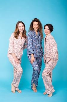 Tre ragazze che indossano pigiami colorati divertendosi sull'azzurro