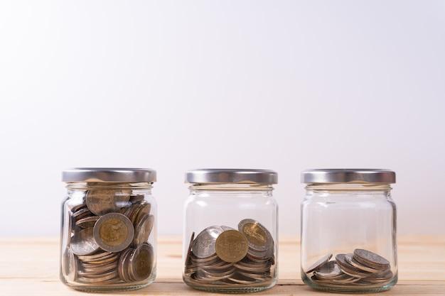 Tre barattoli di vetro con monete all'interno su tavolo di legno e parete bianca