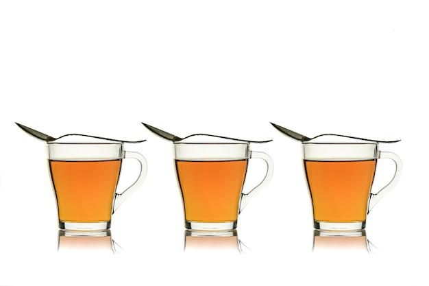 Tre tazze di vetro con tè e cucchiai isolati su bianco