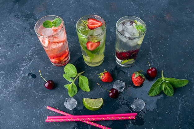 Tre bicchieri di rinfrescante bevanda disintossicante fresca con fragole, lime, ciliegia e menta su sfondo scuro.