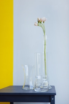 Tre vasi di vetro con fiore bianco su sfondo giallo grigio oggetti antichi di decorazione d'interni