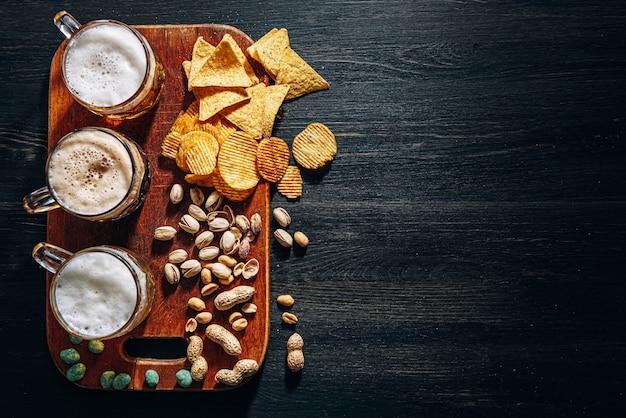 Tre bicchieri di birra artigianale costosa, classica e non filtrata e scura in un bicchiere sul tavolo con uno spuntino a base di arachidi e pistacchi e nachos