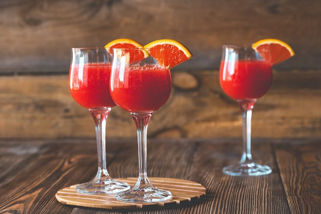 Tre bicchieri di cocktail mimosa sul tavolo di legno