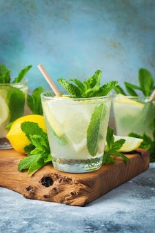 Tre bicchieri di cocktail mojito su tagliere di legno e sfondo di marmo blu