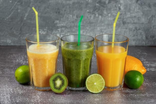 Tre bicchieri di fila con succo d'arancia e frullato di banana arancia e kiwi