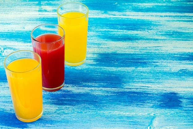 Tre bicchieri di bibite sono su uno sfondo blu