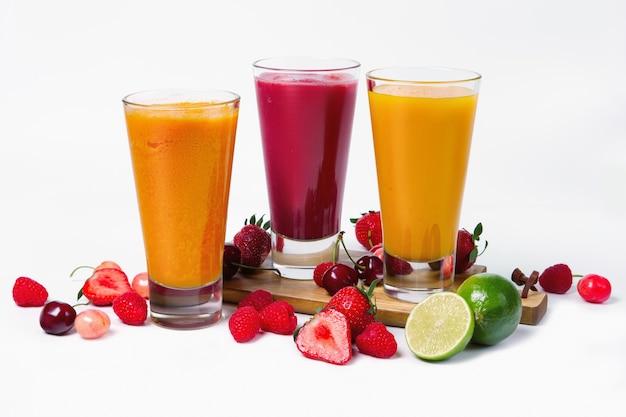Tre bicchieri con frullati di frutta su sfondo bianco