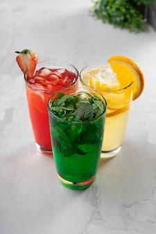 Tre bicchieri con limonate estive di colori rosso, giallo e verde - bibite alla menta, fragola e arancia in bicchieri di vetro trasparente
